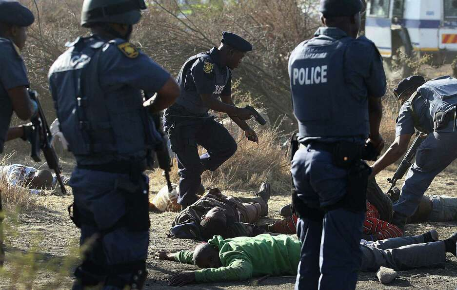 In this Aug. 16, 2012 file photo, police surround the bodies of striking miners after opening fire o