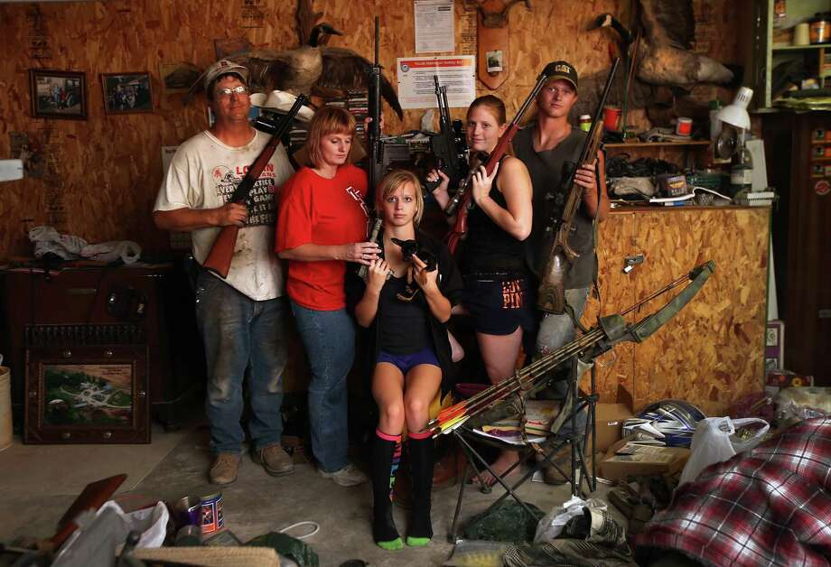 The Becker family, including Darren, his wife Dorthy and their children Renee 15, Katie, 17 and Charlie, 19, show off a small part of the family weapons collection, and their pet Mini Chihuahua, at the Becker farm August 24, 2012 in Logan, Kansas. During hunting season later in the year, the Beckers host guests from around to country. Like many Kansas farmers affected by the record drought, the Beckers are working hard to hang on to their farm, which has been in their family for five generations. Most of Kansas is still in extreme or exceptional drought, despite recent lower temperatures and thunderstorms, according to the University of Nebraska's Drought Monitor. The record-breaking drought, which has affected more than half of the continental United States, is expected to drive up food prices by 2013 due to lower crop harvests and the adverse effect on the nation's cattle industry. Photo: John Moore, Getty Images / 2012 Getty Images
