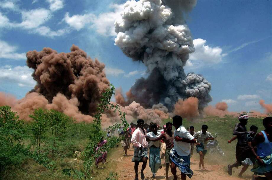 In this Sept. 5, 2012 file photo, people run for cover as smoke rises from the site of a fire at a fireworks factory on the outskirts of Sivakasi, about 500 kilometers (310 miles) southwest of Chennai, India.  Police in southern India arrested six employees of the fireworks factory for a massive blaze that killed 40 workers and injured 60 others. Photo: Uncredited, ASSOCIATED PRESS / A2012