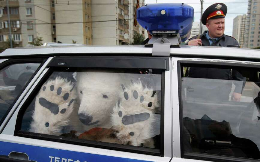 A Greenpeace activist, dressed as a polar bear, sits inside a police car after being detained outsid