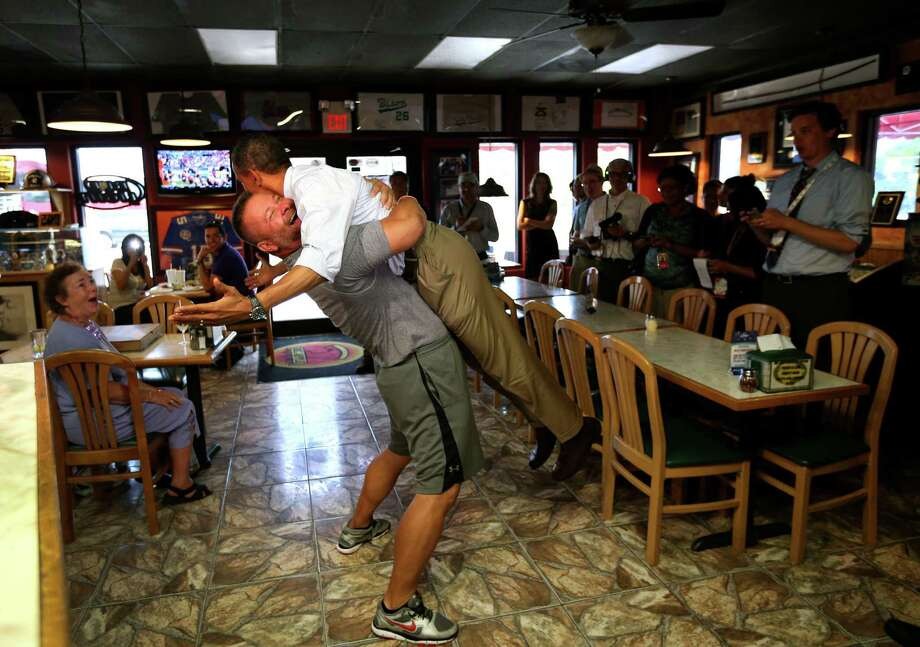 President Barack Obama is lifted into the air while receiving a hug from Scott Van Duzer, owner of Big Apple Pizza, during a campaign stop in Ft. Pierce, Fla., Sept. 9, 2012. Photo: DOUG MILLS, NYT / TEST