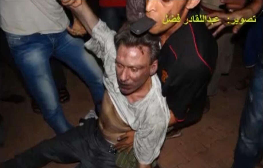 "In this Sept. 11, 2012 file photo, this still image included in a video obtained by the Associated Press from Fahd al-Bakoush, a freelance videographer and activist, which has been authenticated based on its contents and other AP reporting, shows the body of U.S. Ambassador Chris Stevens being moved by Libyan civilians trying to rescue him after gunmen and protesters rampaged through the U.S. consulate in Benghazi, Libya. The group of Libyans had stumbled across Stevens' seemingly lifeless form inside a dark room and didn't know who he was, only that he was a foreigner, al-Bakoush and two other witnesses told the AP. The Arabic script in the photo translates into English as, ""photo Fahd al-Bakoush."" Photo: Fahd Al-Bakoush, ASSOCIATED PRESS / A2012"