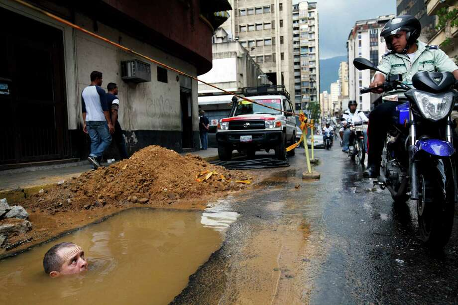 In this Sept. 26, 2012 file photo, a worker is seen partially submerged under water as he tries to repair a broken pipe in Caracas, Venezuela. Photo: Rodrigo Abd, ASSOCIATED PRESS / AP2012