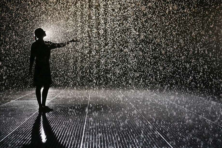 A woman experiences the 'Rain Room' art installation by 'Random International' in The Curve at the Barbican Centre on October 3, 2012 in London, England. The 'Rain Room' is a 100 square meter field of falling water which visitors are invited to walk into with sensors detecting where the visitor are standing. The installation opens to the public on October 4, 2012 and runs until March 3, 2013. Photo: Oli Scarff, Getty Images / 2012 Getty Images