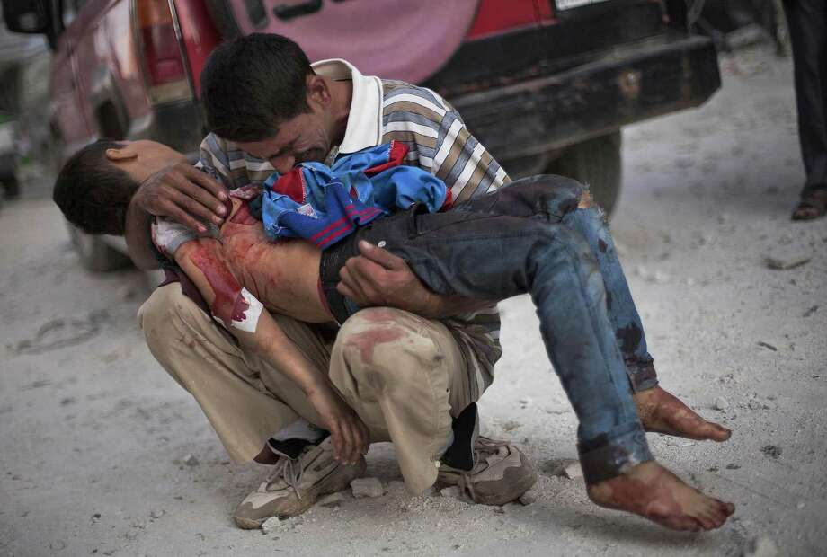 In this Oct. 3, 2012 file photo, a Syrian man cries while holding the body of his son killed by the Syrian Army near Dar El Shifa hospital in Aleppo, Syria. Photo: Manu Brabo, ASSOCIATED PRESS / AP2012