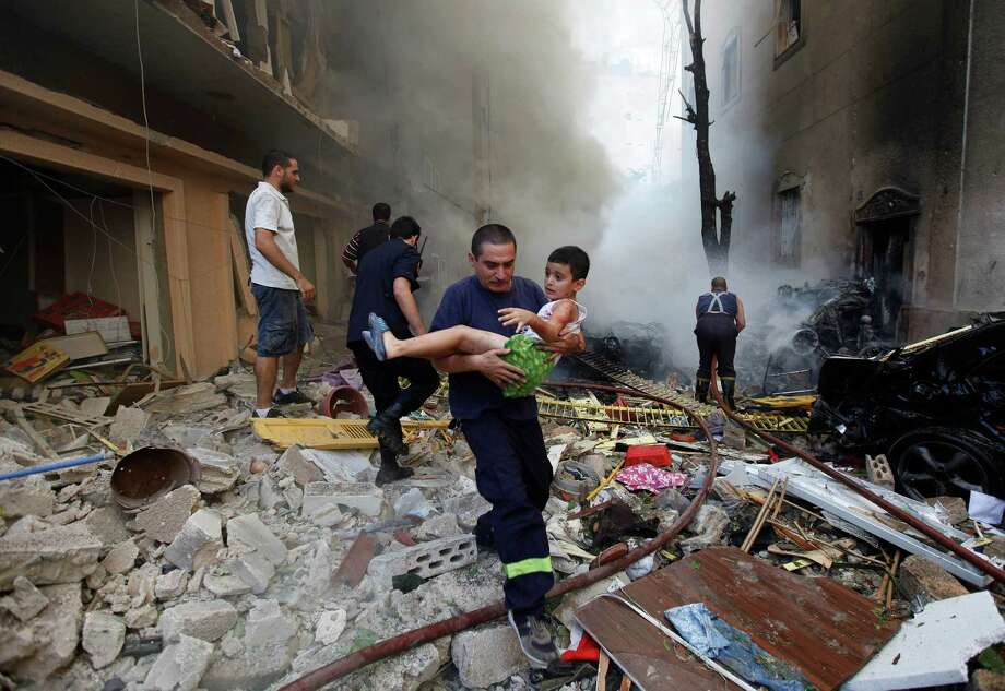 In this Oct. 19, 2012 file photo, a Lebanese rescue man, carries an injured boy at the scene of an explosion in the mostly Christian neighborhood of Achrafiyeh, Beirut, Lebanon. A car bomb ripped through eastern Beirut, shearing the balconies of off residential buildings and sending bloodied victims pouring out into the streets in the most serious blast this city has seen in years. Photo: Hussein Malla, ASSOCIATED PRESS / AP2012