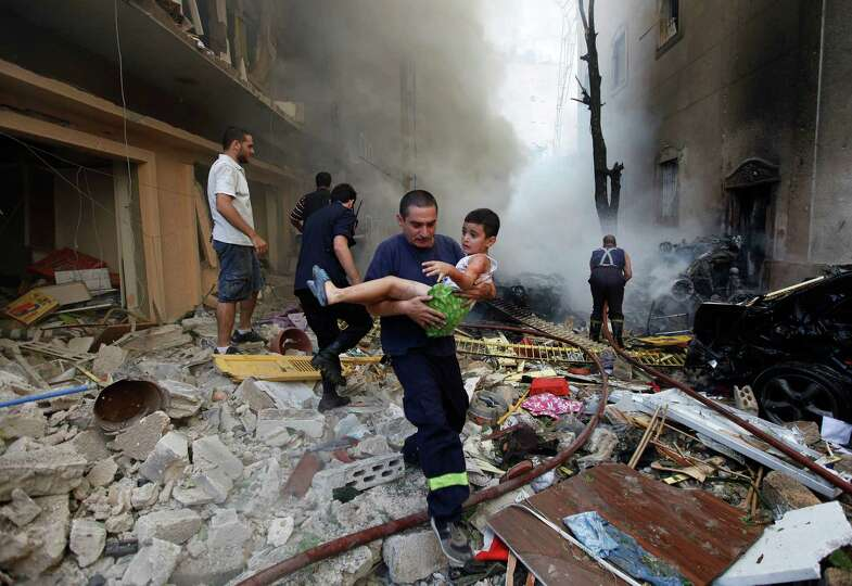 In this Oct. 19, 2012 file photo, a Lebanese rescue man, carries an injured boy at the scene of an e