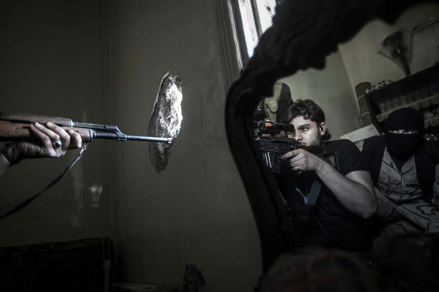 In this Oct. 29, 2012 file photo, a rebel sniper aims at a Syrian army position, seen with another r