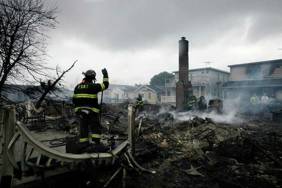 A fire fighter surveys the smoldering ruins of a house in the Breezy Point section of New York, Tuesday, Oct. 30, 2012. More than 50 homes were destroyed in a fire which swept through the oceanfront  community during superstorm Sandy. Photo: Mark Lennihan, ASSOCIATED PRESS / The Associated Press2012