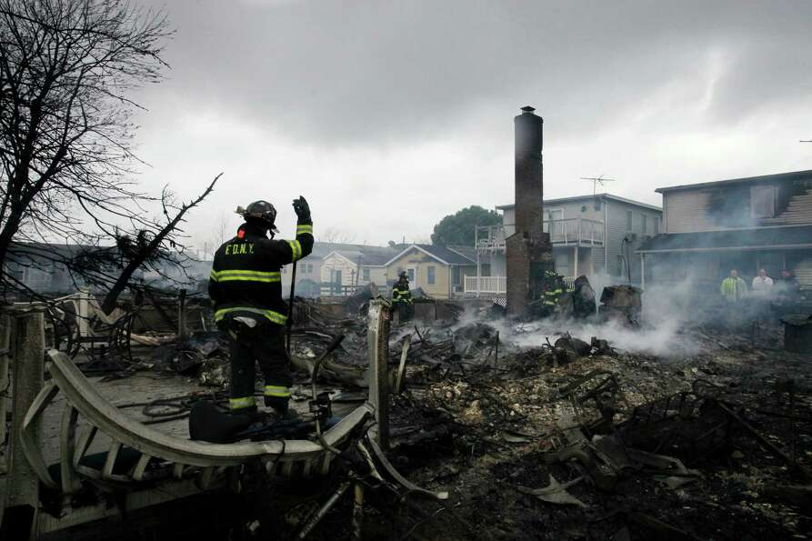 A fire fighter surveys the smoldering ruins of a house in the Breezy Point section of New York, Tues