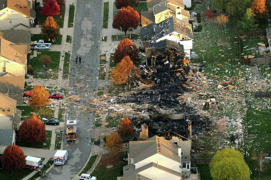 In this Nov. 11, 2012 file aerial photo, the two homes that were leveled and the numerous neighboring homes that were damaged from a massive explosion that sparked a huge fire and killed two people are shown in Indianapolis.  Nearly three dozen homes were damaged or destroyed, and seven people were taken to a hospital with injuries. The powerful nighttime blast shattered windows, crumpled walls and could be felt at least three miles away. Authorities have said they believe the explosion was intentional and caused by natural gas but have released no other details. Photo: Matt Kryger, ASSOCIATED PRESS / A2012