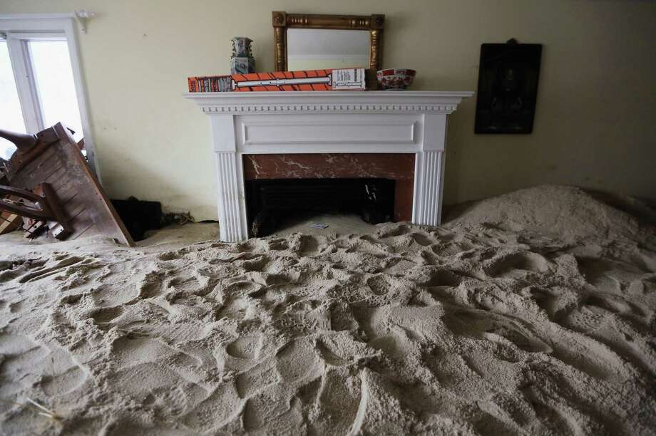 A living room is filled with sand washed in by Superstorm Sandy on November 14, 2012 in Point Pleasant Beach, New Jersey. Many residents of the hard hit seaside town remain without power following Superstorm Sandy. Photo: Mario Tama, Getty Images / 2012 Getty Images
