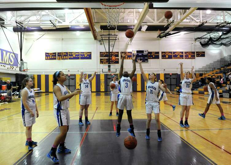 Shaker's teammates warm up after half time during their girls high school basketball game against Ge