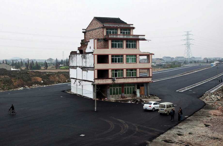 In this Nov. 22, 2012 file photo, people stand near a house sitting in the middle of a new main road on the outskirts of Wenling city in east China's Zhejiang province.  Authorities have demolished the five-story home that stood incongruously in the middle of a new main road and had become the latest symbol of resistance by Chinese homeowners against officials accused of offering unfair compensation. Photo: Uncredited, ASSOCIATED PRESS / A2012