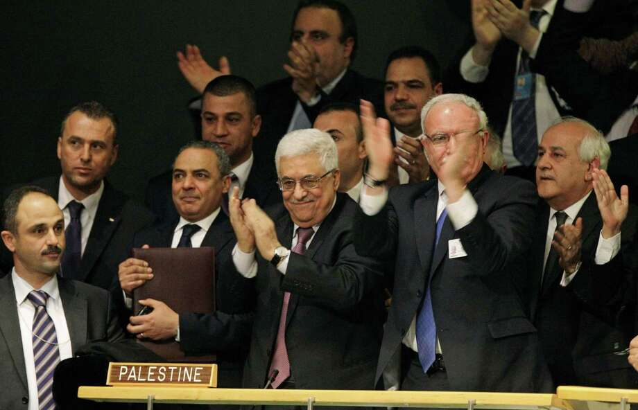 In this Nov. 29, 2012 file photo, members of the Palestinian delegation react as they surround Palestinian President Mahmoud Abbas, center, applauding, during a meeting of the United Nations General Assembly after a vote on a resolution on the issue of upgrading the Palestinian Authority's status to non-member observer state passed in the United Nations in New York. Photo: Kathy Willens, ASSOCIATED PRESS / The Associated Pres2012