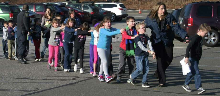 In this Friday, Dec. 14, 2012 file photo provided by the Newtown Bee, Connecticut State Police lead a line of children from the Sandy Hook Elementary School in Newtown, Conn. after a shooting at the school. Photo: Shannon Hicks, Associated Press / Newtown Bee