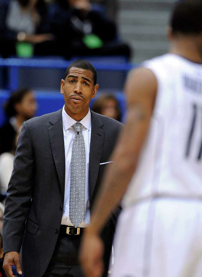 Connecticut coach Kevin Ollie speaks with Ryan Boatright during the first half of an NCAA college basketball game against Washington in Hartford, Conn., Saturday, Dec. 29, 2012. (AP Photo/Fred Beckham) Photo: Fred Beckham, Associated Press / FR153656 AP