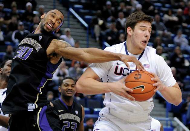Connecticut's Tyler Olander, left, grabs a rebound from Washington's Desmond Simmons during the first half of an NCAA college basketball game in Hartford, Conn., Saturday, Dec. 29, 2012. (AP Photo/Fred Beckham) Photo: Fred Beckham, Associated Press / FR153656 AP