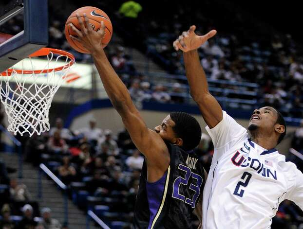 Washington's C.J. Wilcox, left, drives past Connecticut's DeAndre Daniels during the first half of an NCAA college basketball game in Hartford, Conn., Saturday, Dec. 29, 2012. (AP Photo/Fred Beckham) Photo: Fred Beckham, Associated Press / FR153656 AP