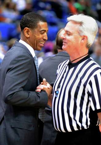 Connecticut coach Kevin Ollie, left, greets an official before the start of his team's NCAA college basketball game against Washington in Hartford, Conn., Saturday, Dec. 29, 2012. Earlier in the afternoon Connecticut officials announced that Ollie had been awarded a new multi-year contract. (AP Photo/Fred Beckham) Photo: Fred Beckham, Associated Press / FR153656 AP