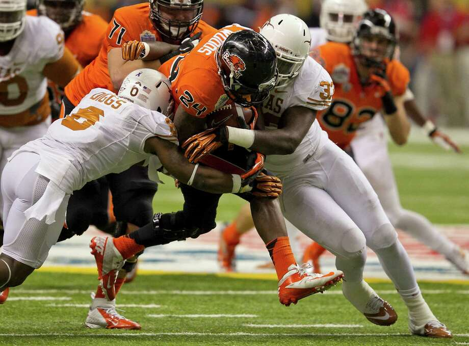 Texas' Quandre Digss (6) and Steve Edmond (33) squeeze Oregon State's Storm Woods (24) during the first half of the Alamo Bowl at the Alamodome in San Antonio, Texas, on Saturday, December 29, 2012. (Rodolfo Gonzalez/Austin American-Statesman/MCT) Photo: RODOLFO GONZALEZ, McClatchy-Tribune News Service / Austin American-Statesman