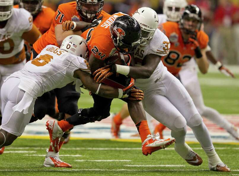 Texas' Quandre Digss (6) and Steve Edmond (33) squeeze Oregon State's Storm Woods (24) during the fi