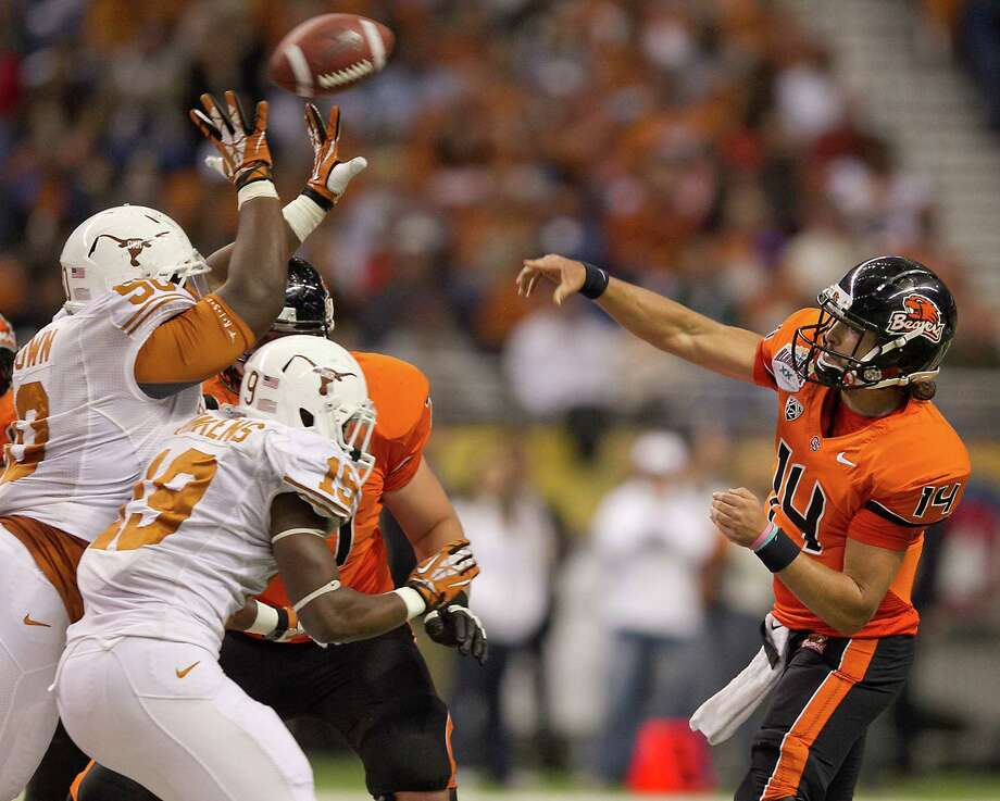 Texas' Malcolm Brown (90) deflects a pass attempt by Oregon State's Cody Vaz (14) during the first half of the Alamo Bowl at the Alamodome in San Antonio, Texas, on Saturday, December 29, 2012. (Rodolfo Gonzalez/Austin American-Statesman/MCT) Photo: RODOLFO GONZALEZ, McClatchy-Tribune News Service / Austin American-Statesman