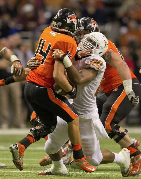 Texas' Alex Okafor (80) sacks Oregon State quarterback Cody Vaz (14) during the first half of the Al