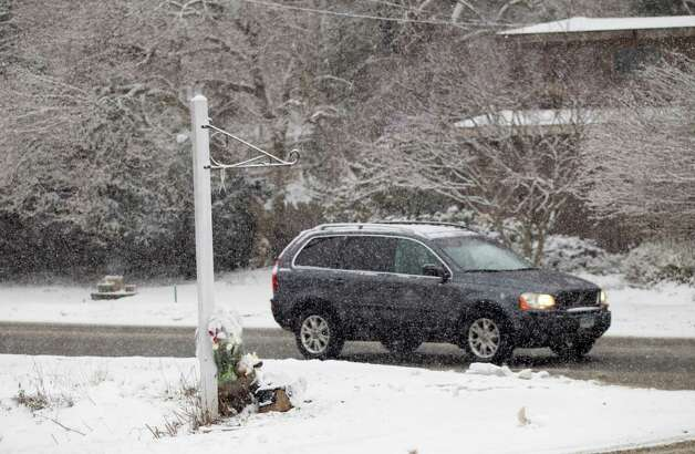 A vehicle drives past the site where a makeshift memorial once stood near Sandy Hook Elementary School Saturday, Dec. 29, 2012, in Newtown. Two of the main memorials have been taken down, leaving just a few items left at the site. ( Brett Coomer / Hearst Newspapers ) Photo: Brett Coomer, Brett Coomer/Hearst Newspapers / The News-Times