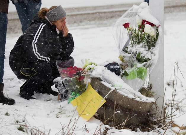 Carmen Faria, of Miami, kneels at the site where a makeshift memorial once stood near Sandy Hook Elementary School Saturday, Dec. 29, 2012, in Newtown. Two of the main memorials have been taken down, leaving just a few items left at the site. ( Brett Coomer / Hearst Newspapers ) Photo: Brett Coomer, Brett Coomer/Hearst Newspapers / The News-Times
