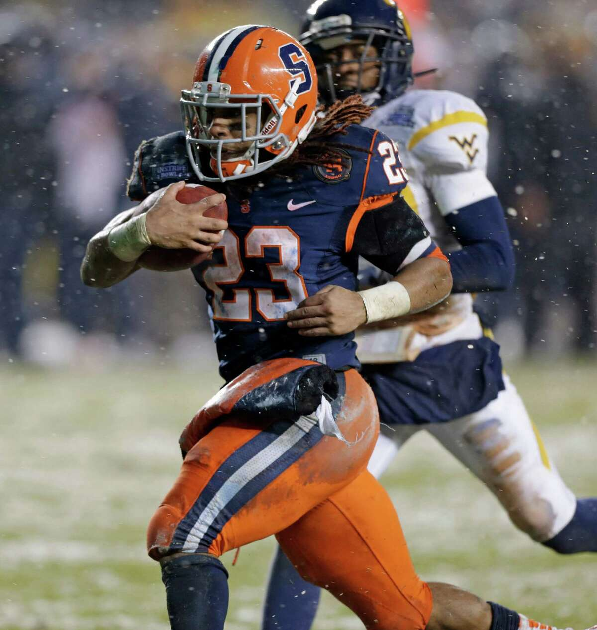 With West Virginia cornerback Pat Miller, rear, in pursuit, Syracuse running back Prince-Tyson Gulley (23) heads for the end zone for a second-quarter touchdown in the Pinstripe Bowl NCAA college football game at Yankee Stadium in New York, Saturday, Dec. 29, 2012. (AP Photo/Kathy Willens)