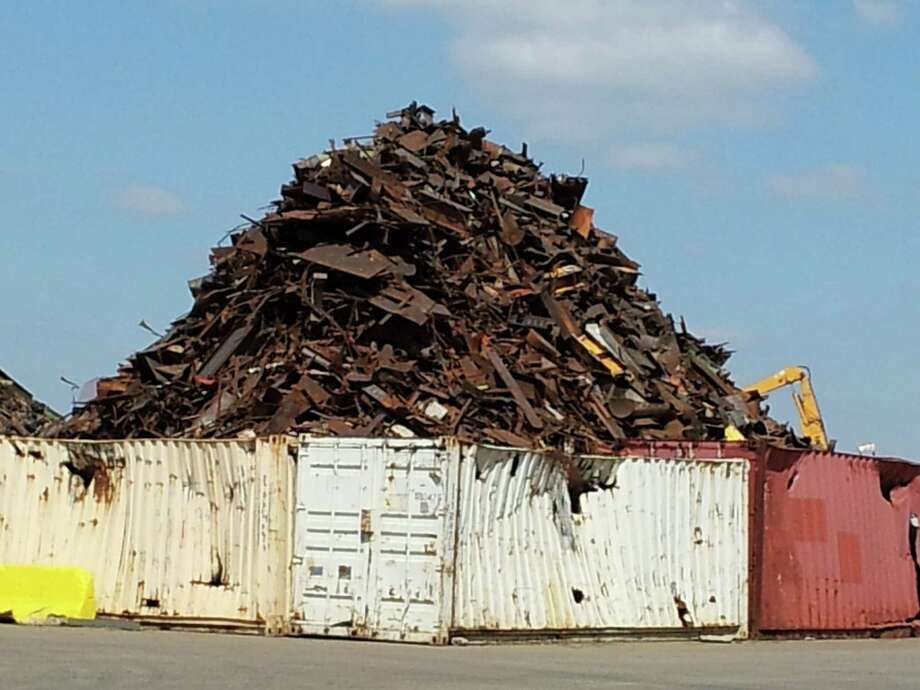 A mountain of scrap metal sits at Texas Port Recycling in Houston's Manchester neighborhood. City officials say the operation has taken steps to reduce emissions and explosions, but residents still complain of smoke. Photo: Ingrid Lobet