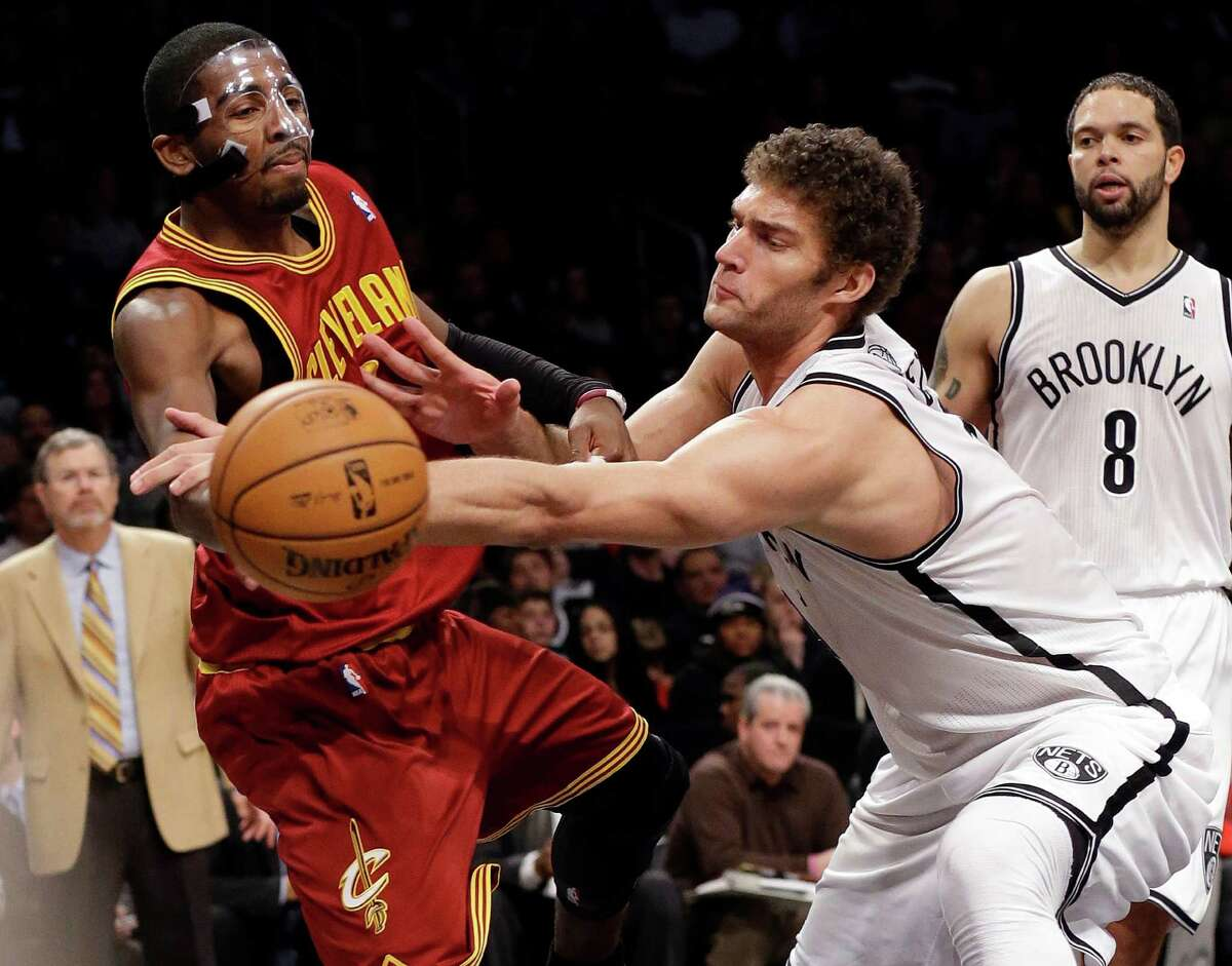 Brooklyn Nets' Brook Lopez (11) defends Cleveland Cavaliers' Kyrie Irving (2) as Nets' Deron Williams (8) watches during the second half of an NBA basketball game Saturday, Dec. 29, 2012, in New York. Lopez scored 35 points as the Nets won 103-100. (AP Photo/Frank Franklin II)