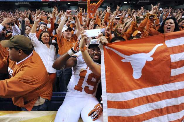 Texas linebacker Peter Jinkens makes a picture of himself with fans after the Longhorns defeated Oregon State, 31-27, in the Valero Alamo Bowl in the Alamodome on Saturday, Dec. 29, 2012. Photo: Billy Calzada, Express-News / SAN ANTONIO EXPRESS-NEWS
