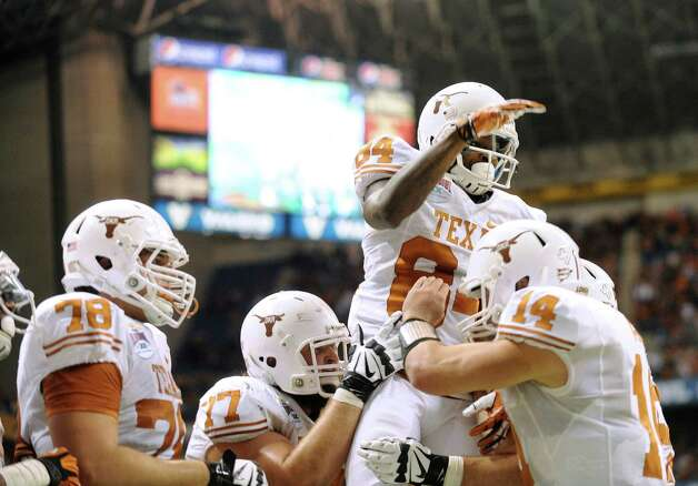 Marquise Goodwin, top right, and Texas teammates celebrate after Goodwin caught the game-winning touchdown pass against Oregon State in the Valero Alamo Bowl on Saturday, Dec. 29, 2012. The Longhorns won, 31-27 over Oregon State. Photo: Billy Calzada, Express-News / SAN ANTONIO EXPRESS-NEWS