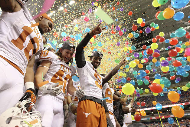 Texas players D.J. Grant (18), Matthew Zapata (40) and Jeremy Hills (05) join other players on the podium to celebrate their victory over Oregon State in the Valero Alamo Bowl on Saturday, Dec. 29, 2012. Texas won, 31-27. Photo: Kin Man Hui, Express-News / © 2012 San Antonio Express-News