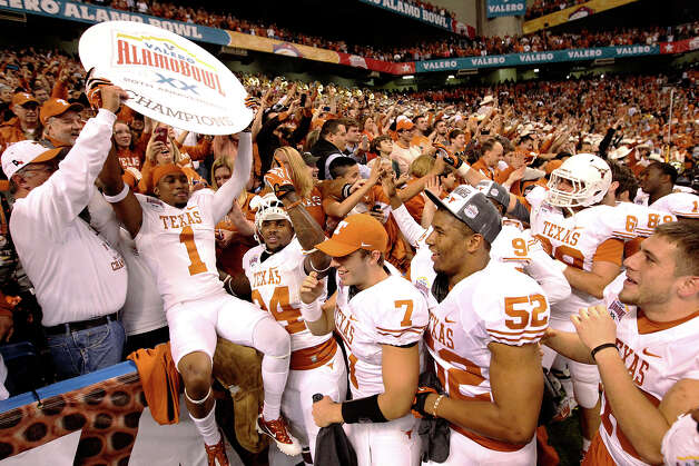 Texas' Mike Davis (01) holds a sign to signify the Longhorns' victory over Oregon State as fellow players and fans celebrate at the Valero Alamo Bowl on Saturday, Dec. 29, 2012. Texas won, 31-27. Photo: Kin Man Hui, Express-News / © 2012 San Antonio Express-News