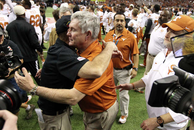 Texas head coach Mack Brown (right) goes to hug Oregon State head coach Mike Riley after the Longhorns defeated the Beavers in the Valero Alamo Bowl on Saturday, Dec. 29, 2012. Texas won, 31-27. Photo: Kin Man Hui, Express-News / © 2012 San Antonio Express-News
