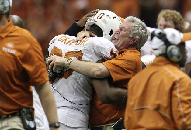 Texas head coach Mack Brown hugs player Alex Okafor (80) after the Longhorns stopped the Oregon State offense late in the fourth quarter in the Valero Alamo Bowl on Saturday, Dec. 29, 2012. Texas won, 31-27. Photo: Kin Man Hui, Express-News / © 2012 San Antonio Express-News