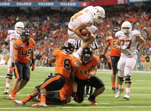 Texas quarterback David Ash (14) leaps over Oregon State defenders Tyrequek Zimmerman (08), Feti Unga (41) and Jordan Poyer (14) to score a touchdown in the second half that sparked a comeback for the Longhorns in the Valero Alamo Bowl on Saturday, Dec. 29, 2012. Texas won, 31-27. Photo: Kin Man Hui, Express-News / © 2012 San Antonio Express-News