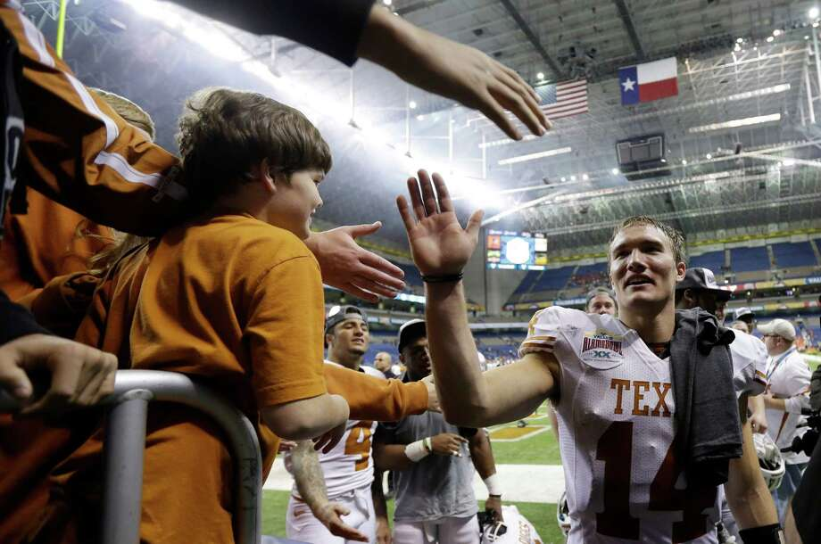 Texas' David Ash, right, celebrates with fans following the team's win over Oregon State in the Alamo Bowl NCAA football game, Saturday, Dec. 29, 2012, in San Antonio.  Texas won 31-27. (AP Photo/Eric Gay) Photo: Eric Gay, Associated Press / AP