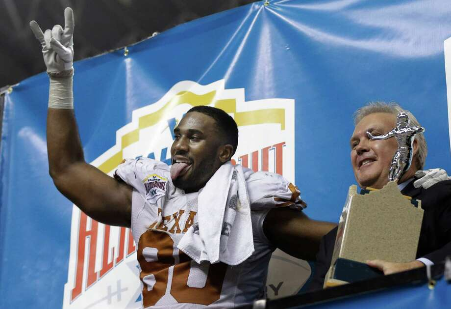 Texas' Alex Okafor, left, reacts as he receives his defensive player of the game trophy following their win over Oregon State in the Alamo Bowl NCAA football game, Saturday, Dec. 29, 2012, in San Antonio.  Texas won 31-27. (AP Photo/Eric Gay) Photo: Eric Gay, Associated Press / AP