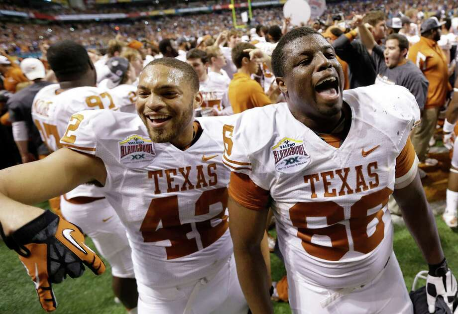 Texas' Caleb Bluiett (42) and Sedrick Flowers (66) celebrate following their win in the Alamo Bowl NCAA football game, Saturday, Dec. 29, 2012, in San Antonio.  Texas won 31-27. (AP Photo/Eric Gay) Photo: Eric Gay, Associated Press / AP