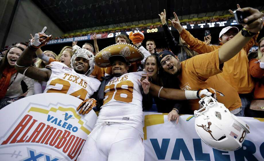 Texas' Joe Bergeron, left, and Cedric Reed (88) celebrate with fans following their win in the Alamo Bowl NCAA football game, Saturday, Dec. 29, 2012, in San Antonio.  Texas won 31-27. (AP Photo/Eric Gay) Photo: Eric Gay, Associated Press / AP