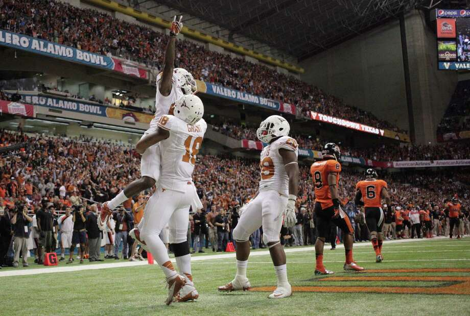 Texas wide receiver Marquise Goodwin is lifted after his 36-yard touchdown catch in the fourth quarter against Oregon State in the Alamo Bowl NCAA college football game Saturday, Dec. 29, 2012, in San Antonio. Texas won 31-27. (AP Photo/The Daily Texan, Lawrence Peart) Photo: Lawrence Peart, Associated Press / The Daily Texan