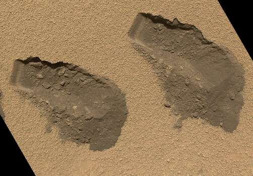 "This picture provided by NASA on December 3, 2012 shows a view of the third (L) and fourth (R) trenches made by the 1.6-inch-wide (4cm) scoop on NASA's Mars rover Curiosity in October 2012. The image was acquired by the Mars Hand Lens Imager (MAHLI) on October 31, 2012 and shows some of the details regarding the properties of the ""Rocknest"" wind drift sand. The upper surface of the drift is covered by coarse sand grains approximately 0.02 to 0.06 inches (0.5 to 1.5 millimeters) in size. These coarse grains are mantled with fine dust, giving the drift surface a light brownish red color. The coarse sand is somewhat cemented to form a thin crust about 0.2 inches (0.5 centimeters) thick. Evidence for the crusting is seen by the presence of angular clods in and around the troughs and in the sharp, jagged indentations and overhangs on one wall of each trench (the walls closest to the top of this figure). Beneath the crust surface, as revealed in the scoop troughs and the piles of sediment on the right side of each, is finer sand, which is darker brown as compared with the dust on the surface. The left end of each trough wall shows alternating light and dark bands, indicating that the sand inside the drift is not completely uniform. This banding might result from different amounts of infiltrated dust, chemical alteration or deposition of sands of slightly different color. Photo: NASA, AFP/Getty Images / AFP"