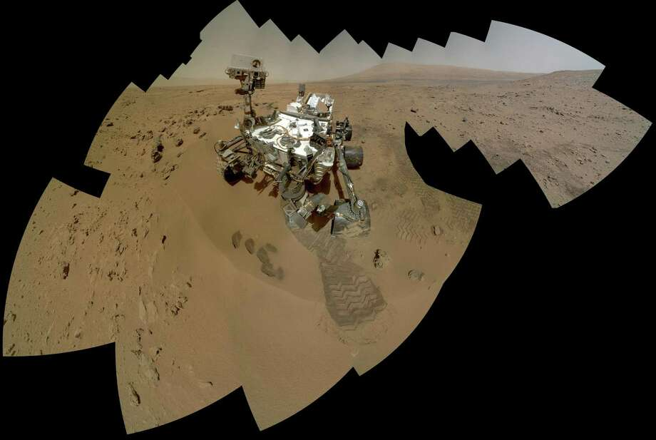 "This picture provided by NASA on December 11, 2012 shows a self portrait of NASA's Curiosity rover captured by the Mars Hand Lens Imager (MAHLI). Dozens of high-resolution images were combined into self-portrait images of the rover. The mosaic shows the rover at ""Rocknest,"" the spot in Gale Crater where the mission's first scoop sampling took place. Four scoop scars can be seen in the regolith in front of the rover. A fifth scoop was collected later. The base of Gale Crater's 3-mile-high (5-kilometer) sedimentary mountain, Mount Sharp, rises on the horizon in the right half of the mosaic. Mountains in the background to the left are the northern wall of Gale Crater. The Martian landscape and the turret on the rover's arm appear inverted within the round, reflective ChemCam instrument at the top of the rover's mast. The rover's robotic arm is not visible in the mosaic. MAHLI, which took the component images for this mosaic, is mounted on a turret at the end of the arm. Wrist motions and turret rotations on the arm allowed MAHLI to acquire the mosaic's component images. Photo: NASA, AFP/Getty Images / AFP"