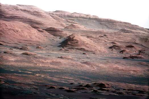 This image provided by NASA shows the base of Mount Sharp on Mars. The Curiosity rover is set to drive toward the mountain in mid-February after drilling into a rock. The image was taken by Curiosity's 100-millimeter Mast Camera on Aug. 23, 2012. Scientists enhanced the color in one version to show the Martian scene under the lighting conditions we have on Earth, which helps in analyzing the terrain. (AP Photo/NASA/JPL-Caltech/MSSS) Photo: Anonymous, Associated Press / NASA/JPL-Caltech/MSSS