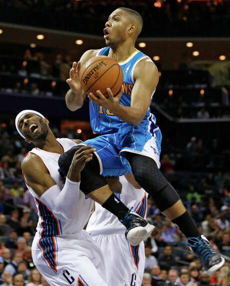 New Orleans Hornets' Eric Gordon, top, runs into Charlotte Bobcats' Hakim Warrick, bottom, as he drives to the basket during the second half. Photo: Chuck Burton, STF / AP