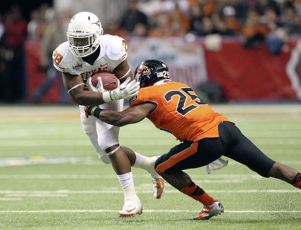 Texas'  Malcolm Brown (28) attempts to break the tackle of Oregon State's Ryan Murphy (25) in the second half of the 2012 Valero Alamo Bowl on Saturday, Dec. 29, 2012. Photo: Kin Man Hui, Express-News / © 2012 San Antonio Express-News